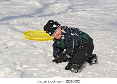 Child in snowball fight in winter snow