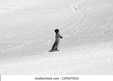 A child is snowboarding down a deserted ski-run. Their face is covered with a helmet and turned away from the camera. The photograph is in black and white.