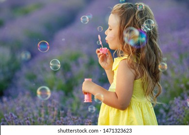 A child with soap bubbles. Little girl in a field with flowers.