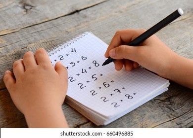 Child solves math examples. Child holds a marker in his hand and writes answers to multiplication examples in notebook. Learning multiplication table concept. Homeschool education.  Kid math studying
