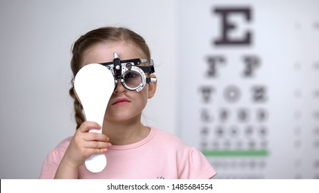 Child in special glasses with eye closed checking vision, astigmatism diagnosis