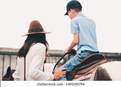 A child with special needs is riding with a close supervision teacher]This is a treatment called Hippotherapy, Life in the education age of disabled children, Happy disability kid concept.