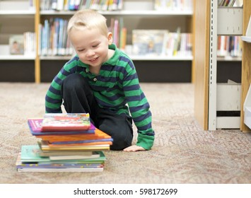 Child Stacking Favorite Books at the Library in the children's storytime area.