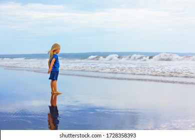 Child stand on black sand sea beach. Dreaming child look at sea surf landscape, breaking storm waves. Solitude concept. Retreat leisure on summer family vacation with kids. Travel lifestyle banner.
