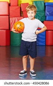 Child standing with a basketball in gym of a school
