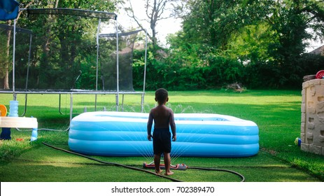 A child standing and considering his options to enjoy in the backyard