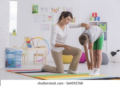 Child standing forward bend while exercising with physiotherapist