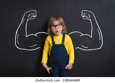 Child standing near chalkboard with muscles on it. Happy superhero kid is ready for kindergarten or daycare. Success, motivation concept. Girl power and feminism concept. Back to school.