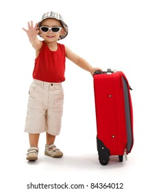 Child standing near luggage, wearing hat and sunglasses, holding his luggage and waving good bye with hand
