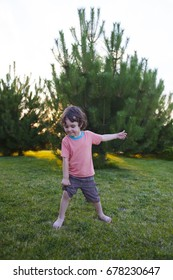 The child is standing on the green grass near the trees.