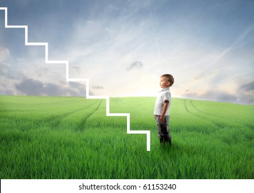 Child standing on a green meadow in front of a stairway