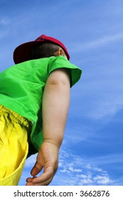 child standing outside over deep blue sky