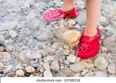 Child standing in shallow water with nice red shoes