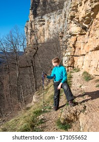 A child stands with alpenstock the rock against the sky