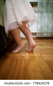 A child stands barefoot on tiptoe on a wooden floor