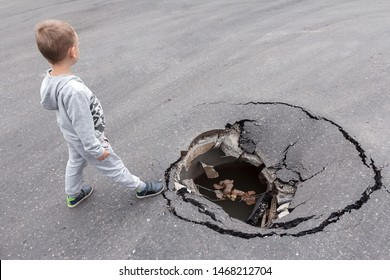 A child stands on the brink of a large pit in the asphalt. Danger of injury to children on a city street. Road surface hole
