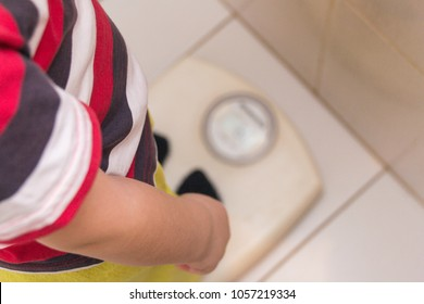 The child stands on the floor scales in a striped T-shirt, the view from the top. Health