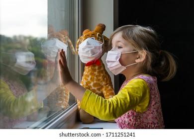 Kind bleibt bei Spielzeug zu Hause. Kleines Mädchen, das nach draußen schaut. Corona-Virus-Prävention.