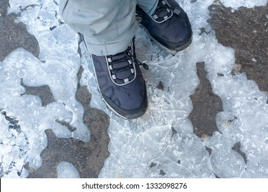 Child steps on frozen puddle with thin ice. Close up.