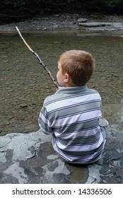 Child with stick enjoying a stream