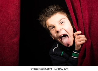 Child stick out his tongue.Appearing beneath the curtain