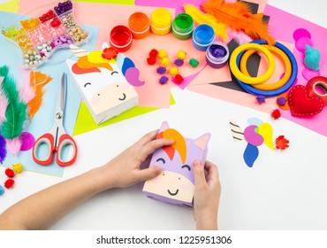 Child sticks hand craftwork unicorn. Unusual gift from paper box. Master class handmade. Favorite hobby. Kindergarten and school.