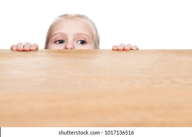 Child sticks his eyes out from under the table and looks sideways, isolated on a white background