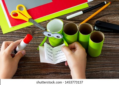 Child sticks together details Paper Roll Pencil Holder the new school year. Welcome back to school. Children's Art Project, needlework, crafts for kids.