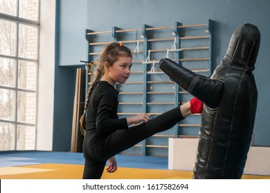 The child strikes with a straight foot on the training manikin. Little girl trains kick on a punching bag. The child is engaged in martial arts in the gym.