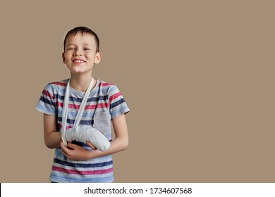 a child in a striped t-shirt with a bandage wrapped around his arm. Arm injury