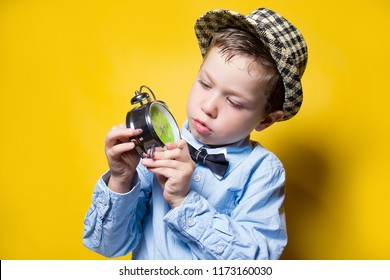 the child is studying the clock in the hat on a yellow background! alarm clock in hand! have to go to school