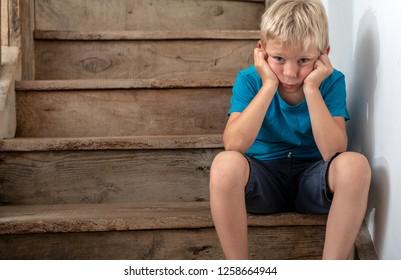 Child sulking in corner on staircase. Sitting in naughty corner.