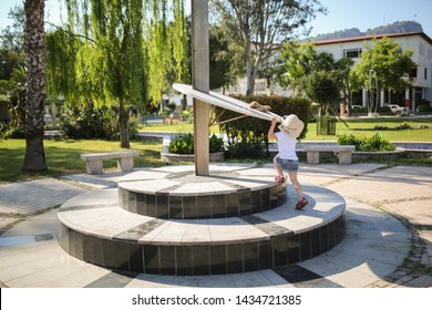 child and sundial, girl plays near sundial in a small square in summer, Kemer, Turkey
