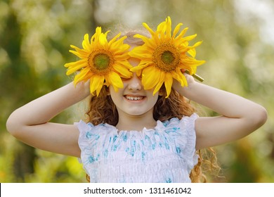 Child with sunflowers in his hand show white teeth; enjoying nature in summer sunny day. Healthcare; freedom and happy childhood concept.