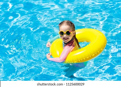 Child with sunglasses in swimming pool. Little girl on inflatable ring. Kid with colorful float. Kids learn to swim and dive in outdoor pool of tropical resort. Sun protection and eye wear. Water fun.