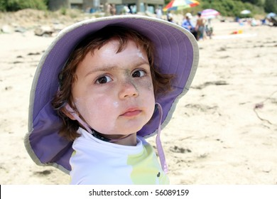 Child with sunscreen and sand on face