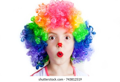 child with a surprised expression, in a clown suit, on a white background, emotion