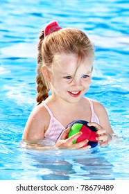 Child  in swimming  pool with ball.