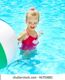 Child  swimming in pool with beach ball.