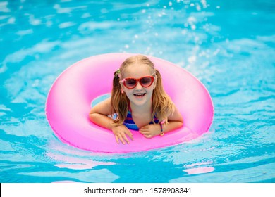 Child in swimming pool floating on toy ring. Kids swim. Colorful rainbow float for young kids. Little girl having fun on family summer vacation in tropical resort. Beach and water toys. Sun protection