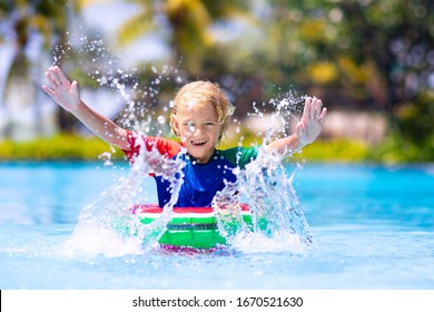 Child in swimming pool floating on toy ring. Kids swim. Colorful rainbow float for young kids. Little boy having fun on family summer vacation in tropical resort. Beach and water toys. Sun protection.