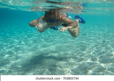 Child swimming underwater in blue transparent sea water