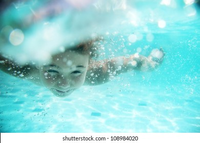 child swimming underwater in sea or pool