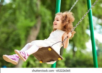 Child swinging on a swing at  playground in the park.