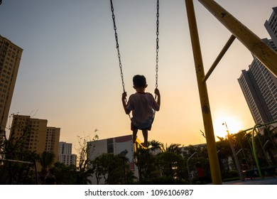 Child swinging on swing in sunset in city with building on background