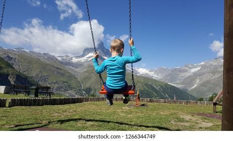 Child swinging in a park overlooking the mountain matterhorn