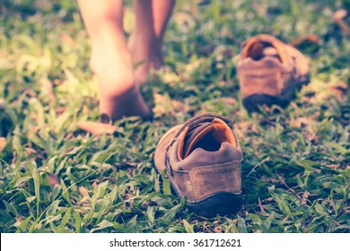 Child take off leather shoes. Close up child's foot learns to walk on grass, reflexology massage. Kid relax in garden. Shallow depth of field (dof), selective focus. Retro style.