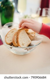 Child take a piece of a bread from the table