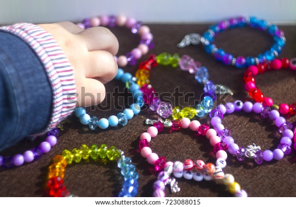 The child takes baby bracelets from colored beads. Bright children's decorations in a box. Buy colorful children's bracelets at hand.