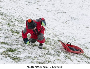 Child taking advantage of snow, pulling a sledge up a hill barely covered with snow.
